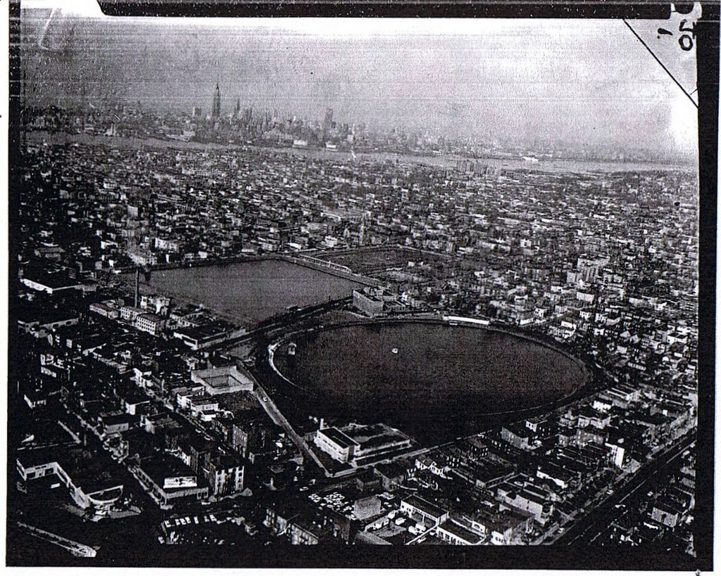 Grainy black and white photo from birds eye view. View of jersey city buildings, reservoir and the New York City skyline.